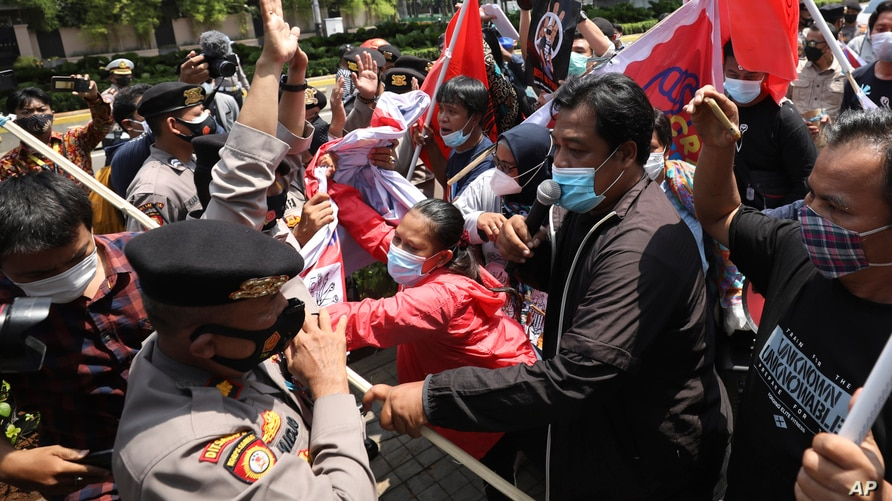 Activists scuffle with police officers as they are dispersed during a rally against Myanmar's military coup near the…