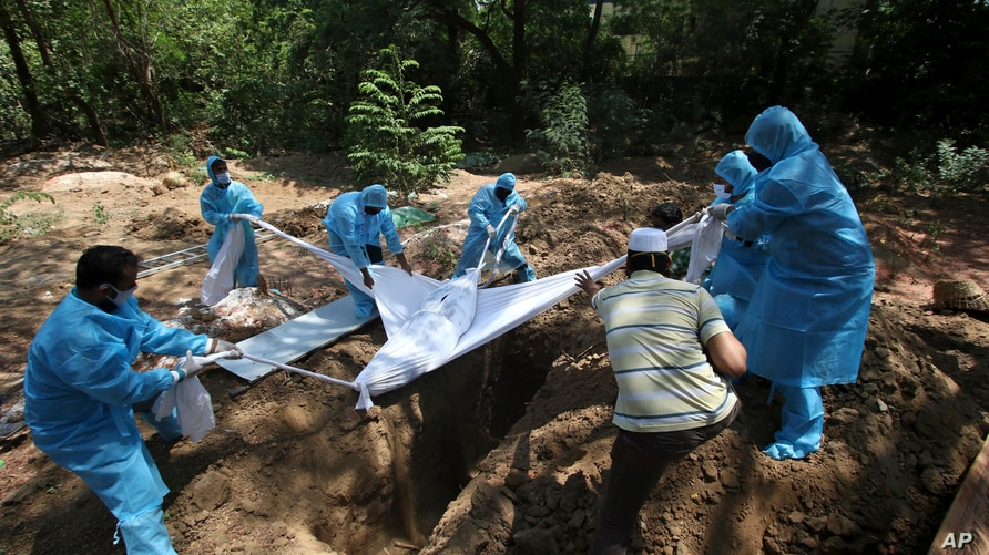 Volunteers and workers bury the body of a COVID-19 victim in Chennai, India, Saturday, June 5, 2021. (AP Photo/R. Parthibhan)