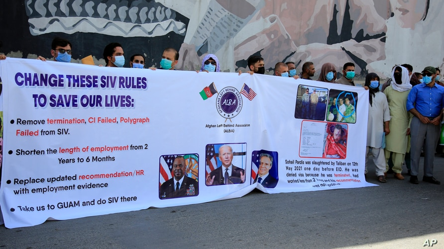 In this June 25, 2021 photo, former Afghan interpreters hold placards during a demonstrations against the US government, in…