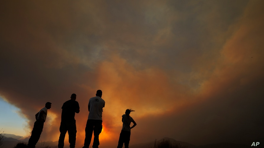 Residents of villages watch a fire in the Larnaca mountain region on Saturday, July 3, 2021. Cyprus has asked fellow European…