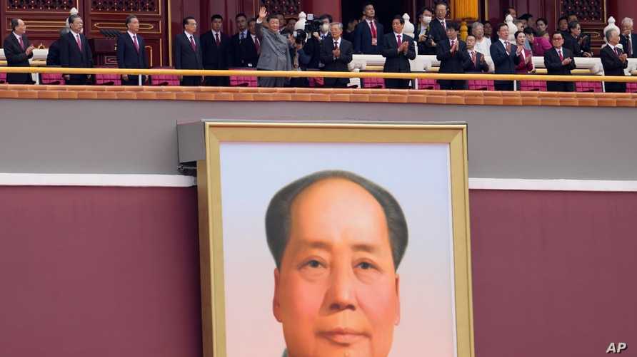Chinese President Xi Jinping, center, waves above a large portrait of the late leader Mao Zedong during a ceremony to mark the…