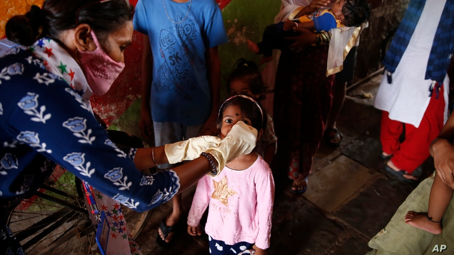 A health worker administers polio drops to children at a slum in Mumbai, India, Sunday, June 27, 2021. Polio is a highly…