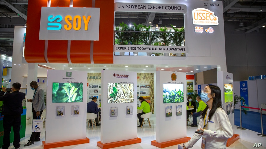 A visitor wearing a face mask walks past a display from the U.S. Soybean Export Council at the China International Import Expo…