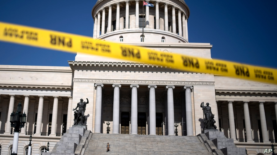 Caution tape blocks the street at the entrance of the National Capitol building in Havana, Cuba, Tuesday, July 13, 2021. Cuban…
