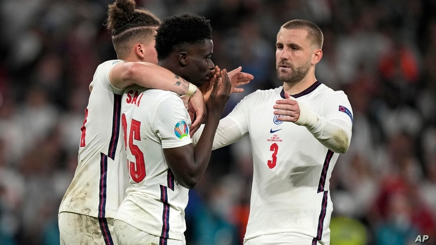 England's Bukayo Saka is comforted after he missed to score the last penalty during the penalty shootout of the Euro 2020…