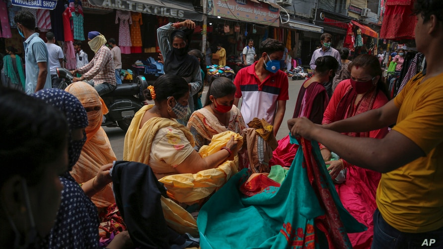 People shop at a market ahead of Eid-al Adha festival in Jammu, India, Sunday, July 18, 2021. (AP Photo/Channi Anand)