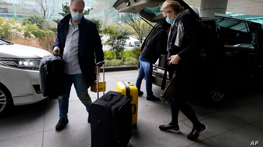 John Watson, left and Thea Koelsen Fischer of the World Health Organization team arrive at the VIP terminal of the airport to…