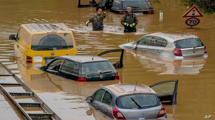 Helpers check for victims in flooded cars on a road in Erftstadt, Germany, Saturday, July 17, 2021. Due to strong rain falls…