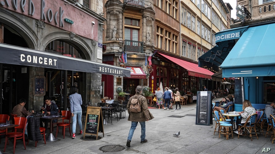 A man walks by restaurants in Lyon, central France, Tuesday, July 13, 2021. Nearly 1 million people in France made vaccine…