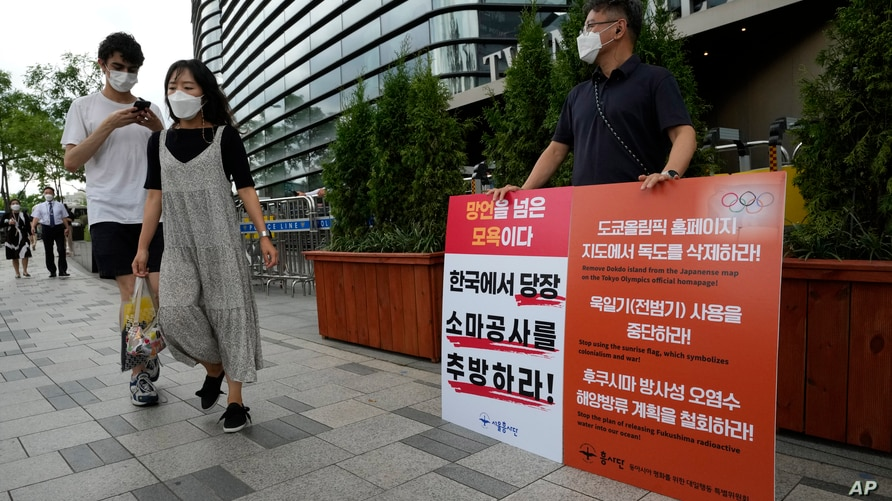 A protester stands to oppose South Korean President Moon Jae-in's possible visit to Japan in front of a building which houses…
