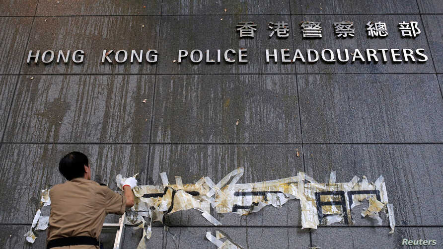 Staff try to clean off marks from thrown eggs and anti-extradition graffiti on the walls of the Hong Kong Police headquarters in Hong Kong, June 22, 2019.