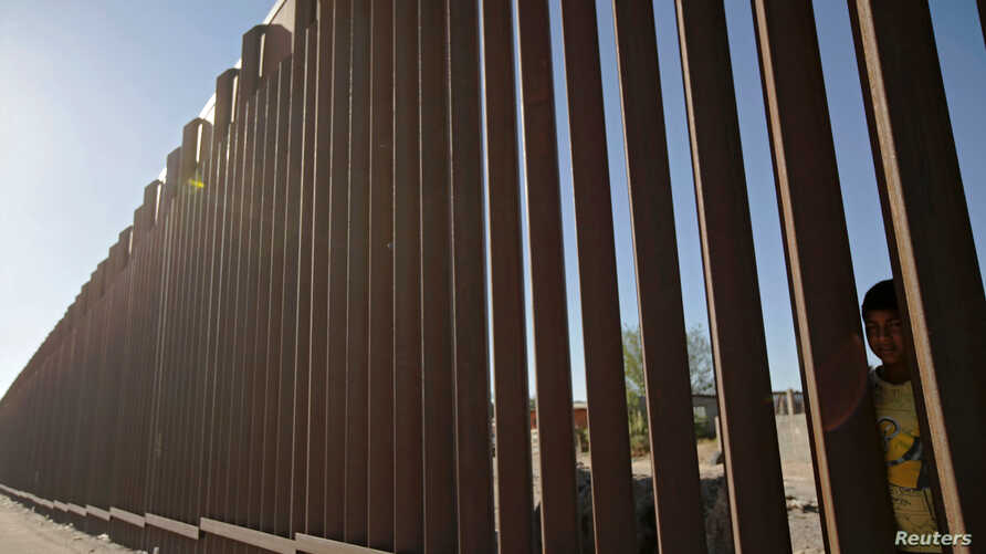 FILE PHOTO: A child looks through the bars of a wall from the side of Ciudad Juarez, Mexico, in this picture taken on the side of El Paso