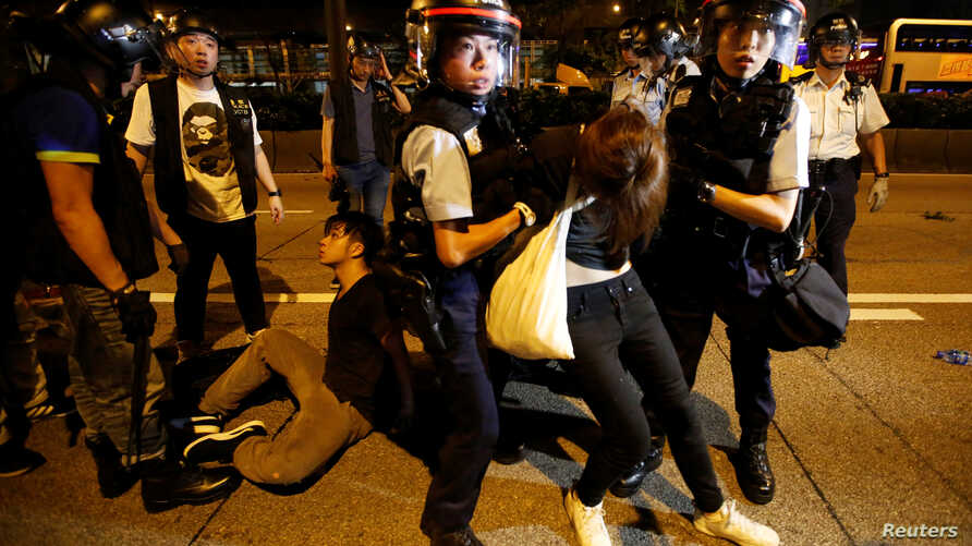 Police officers detain protesters during a protest to demand authorities scrap a proposed extradition bill with China, on Gloucester Road in Hong Kong
