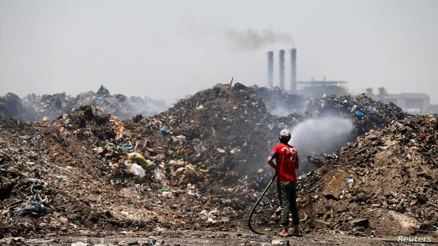 A municipal worker extinguishes a fire inside the garbage at a rubbish dump in Baghdad