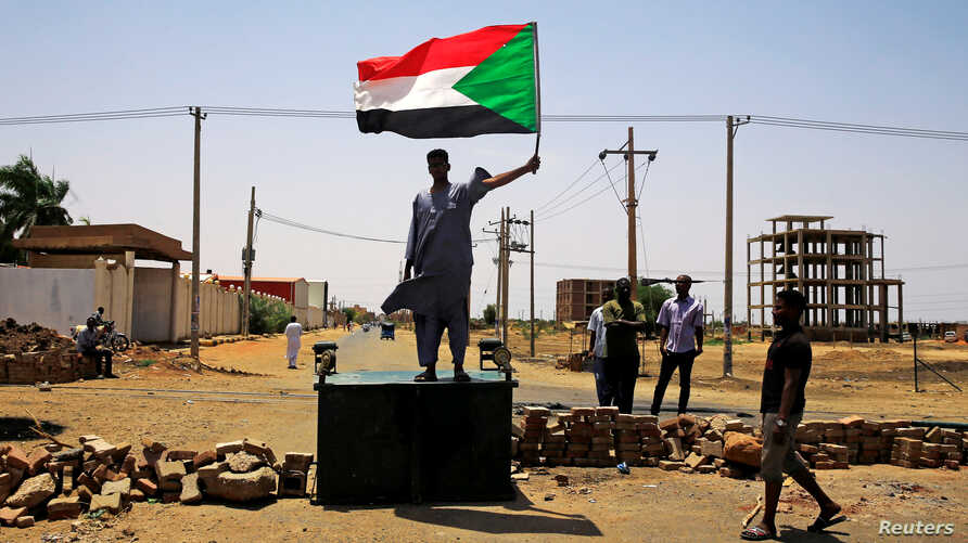 A Sudanese protester holds a national flag as he stands on a barricade along a street, demanding that the country's Transitional Military Council hand over power to civilians, in Khartoum