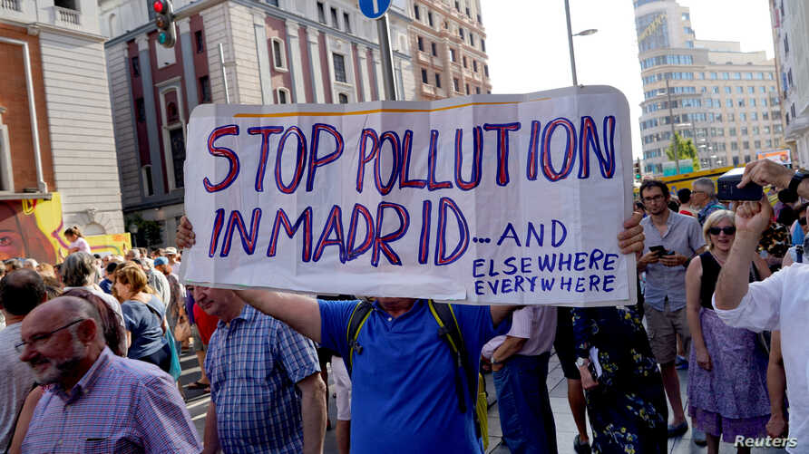 Demonstrators take part in a protest against Madrid's new conservative People's Party (PP) municipal government plans to suspend some anti-car emissions policies in Madrid's city center