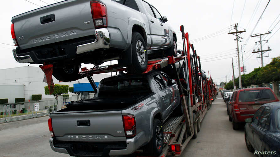A carrier trailer transports Toyota cars for delivery while queuing at the Mexican border customs control to cross into the U.S.