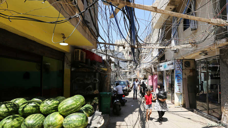 People walk along a street covered with electricity cables at Burj al-Barajneh refugee camp in Beirut