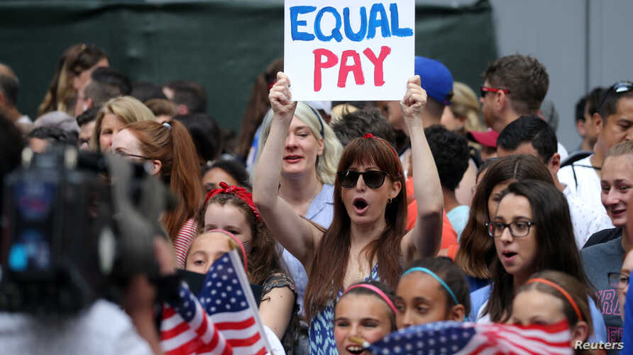Fans along the parade route chant for equal pay as they wait for the team during the ticker-tape parade for the United States women's national soccer team down the canyon of heroes in New York City, July 10, 2019. (Brad Penner-USA TODAY Sports)