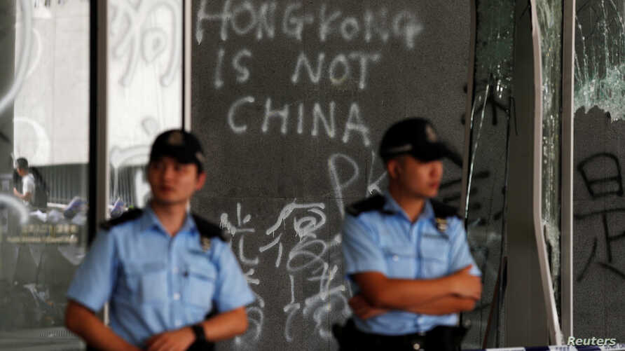 Policemen stand in front of graffiti on the walls of the Legislative Council, a day after protesters broke into the building in Hong Kong, July 2, 2019.