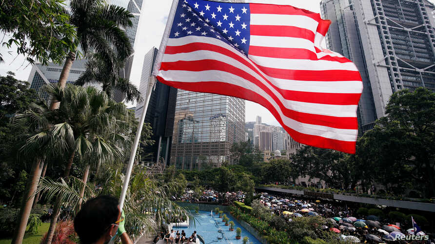 A man holds a U.S. flag as pro-democracy protesters gather at Chater Garden before a march to protest police violence during previous marches, in central Hong Kong, July 28, 2019.