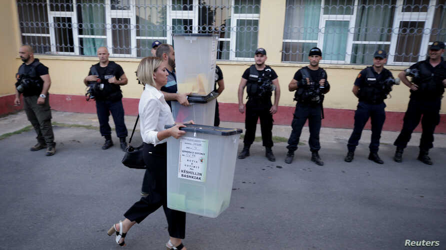 Election workers carry ballot boxes to a local election counting centre in Shkodra, Albania, June 30, 2019.