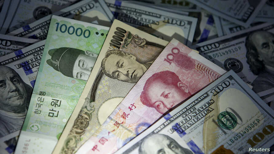 FILE - South Korean won, Chinese yuan and Japanese yen notes are seen with U.S. $100 bill in this illustration taken in Seoul, South Korea, Dec. 15, 2015.