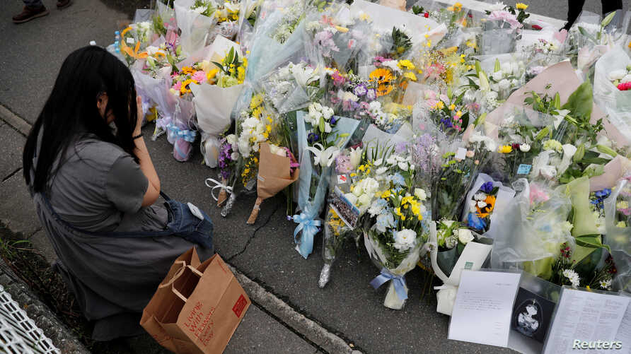 A woman prays in front of a row of flowers placed for victims of the torched Kyoto Animation building in Kyoto, Japan, July 20, 2019.
