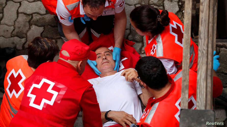 A reveler is helped by medical staff during the running of the bulls at the San Fermin festival in Pamplona, Spain, July 14, 2019.
