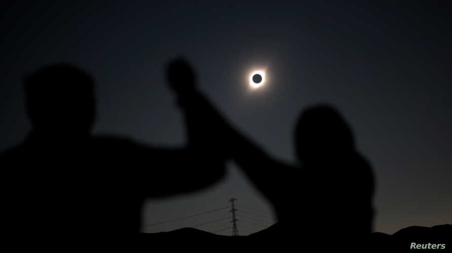 People react while observing a solar eclipse at Incahuasi, a mountain in Chile, July 2, 2019.