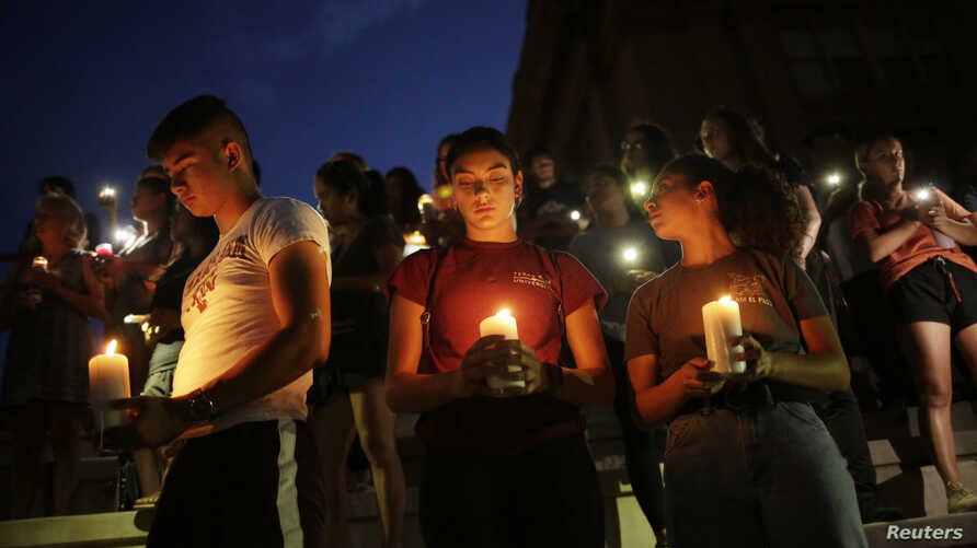 Samuel Lerma, Arzetta Hodges and Desiree Qunitana join mourners at a vigil at El Paso High School after a mass shooting at a Walmart store in El Paso, Texas, Aug. 3, 2019.