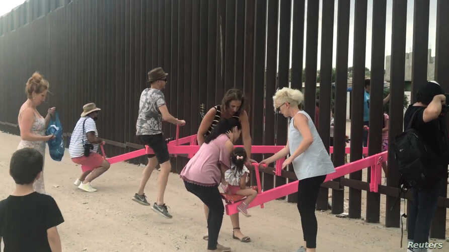 People play on a set of fluorescent pink seesaws across the U.S.-Mexico border in Sunland Park, NM, in this still image taken from social media video, July 28, 2019.