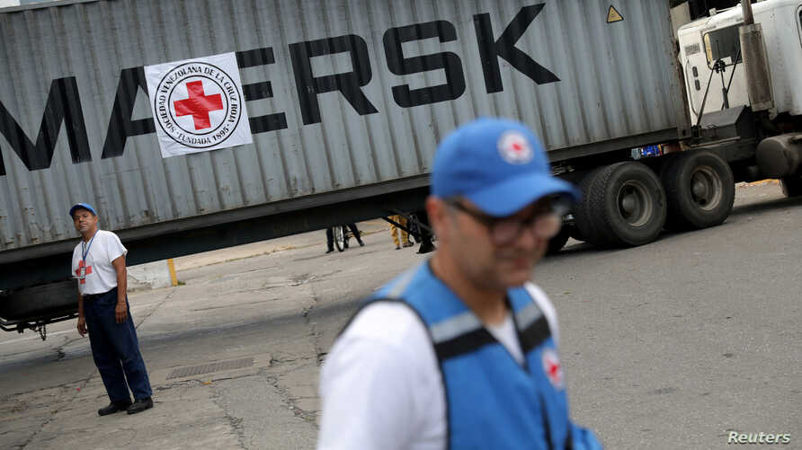 Volunteers stand near a container truck bearing a logo of the International Federation of Red Cross and Red Crescent Societies (IFRC) that arrived carrying humanitarian aid to be stored in a warehouse in Caracas, Venezuela