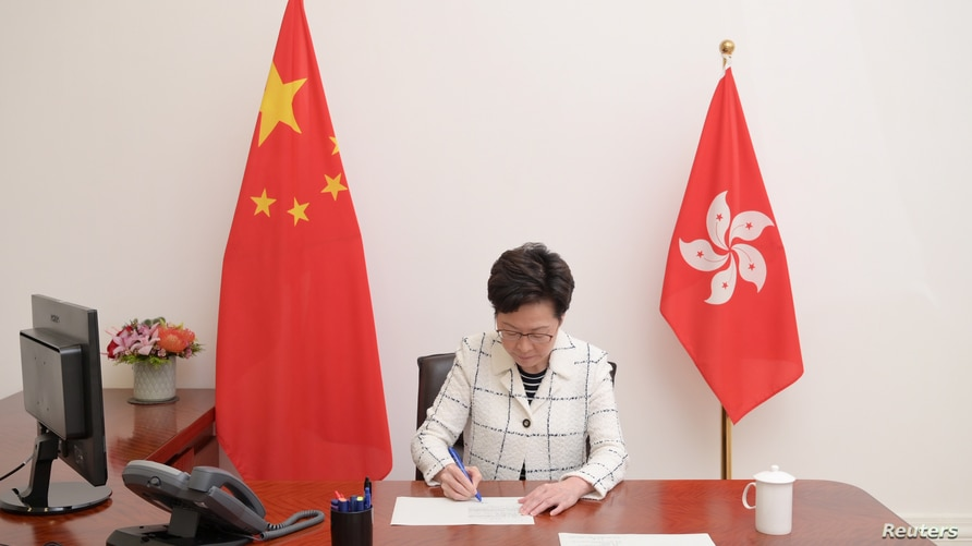 Handout picture of Hong Kong Chief Executive Carrie Lam signing the promulgation of the National Security Law