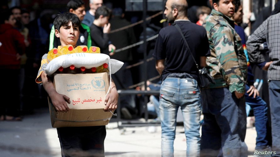 FILE PHOTO: Boy holds a cardboard box of food aid received from World Food Programme in Aleppo's Kalasa district