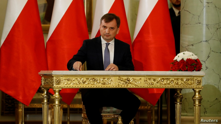 FILE PHOTO: Zbigniew Ziobro signs documents after being designated as Minister of Justice, at the Presidential Palace in Warsaw