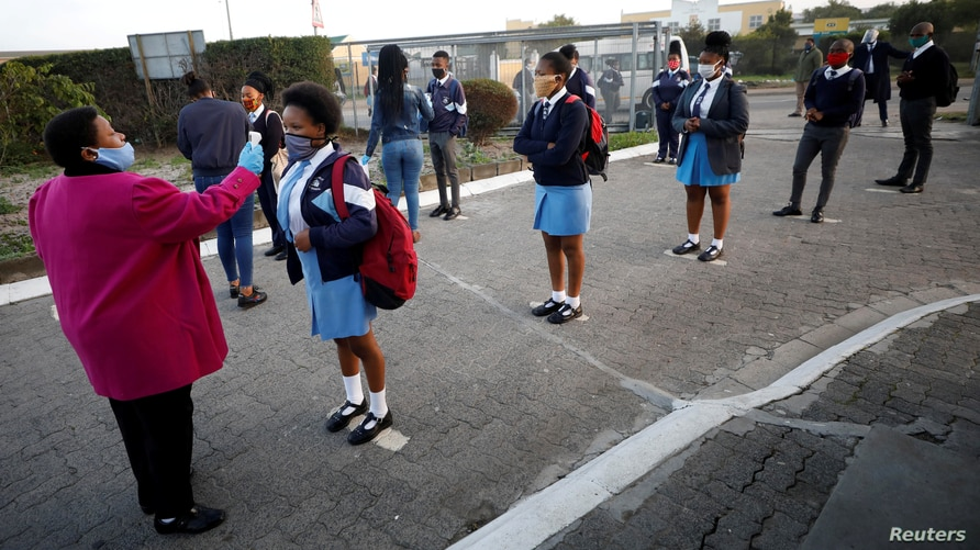 FILE PHOTO: A teacher screens students as schools begin to reopen  after the coronavirus disease (COVID-19) lockdown in Cape Town