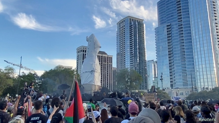 Still image from video of protesters surrounding a statue of Christopher Columbus in Chicago