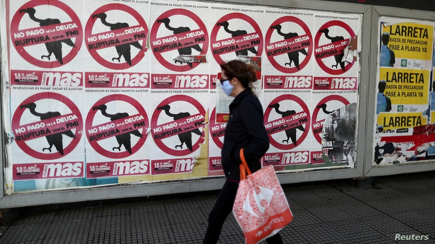 """FILE PHOTO: A pedestrian wearing a protective face mask walks past posters on the street that read """"No to the payment of the debt. Break with the IMF"""", in Buenos Aires"""