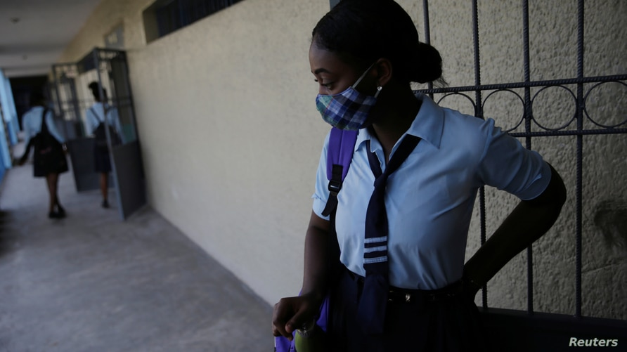 A pupil wearing a face mask to prevent the spread of the coronavirus disease (COVID-19), waits outside a schoolroom for the start of the lessons during the first day of school after holidays, at Lycee National de Petion Ville, in Port au Prince