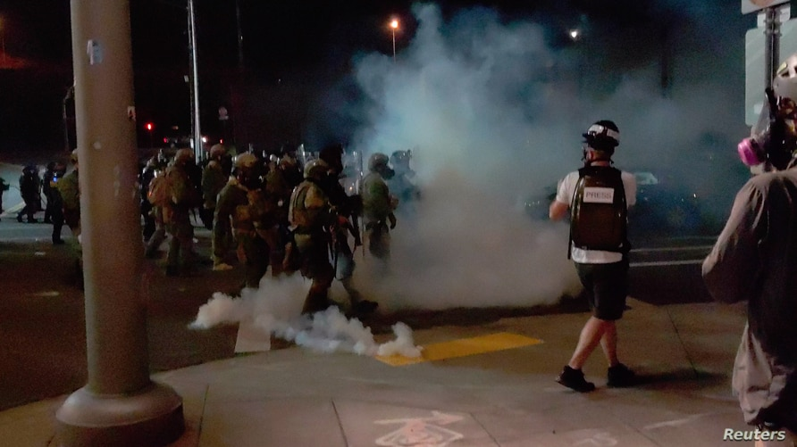 A member of the media stands amid tear gas used by police officers to clear protesters near an Immigration and Customs Enforcement centre in Portland