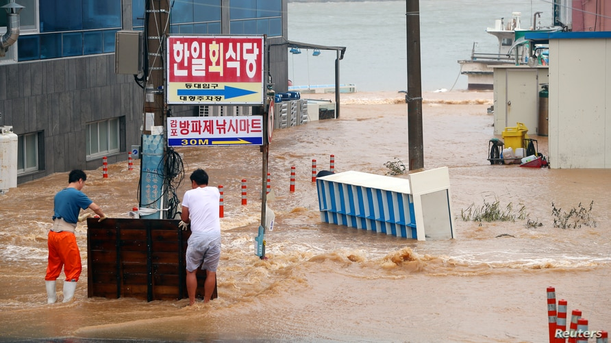 Men stand on a street submerged by typhoon Haishen in Gyeongju