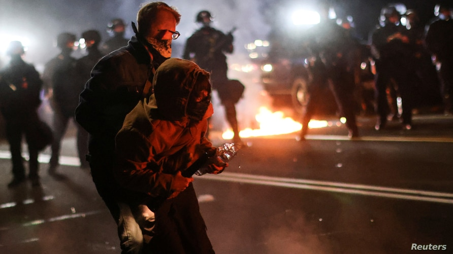 A protester is helped by another to retreat after clashing with the police on the 100th consecutive night of protests against police violence and racial inequality, in Portland, Oregon