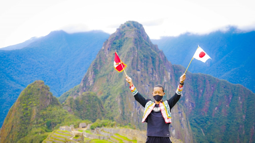 Japanese tourist Jesse Katayama holds a Peruvian and a Japanese flag after becoming the first tourist to visit the Inca citadel during the coronavirus disease (COVID-19) pandemic, in Machu Picchu