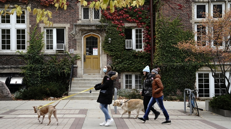 People walk their dogs on the campus of the University of Wisconsin-Madison as the coronavirus disease (COVID-19) outbreak continues in Madison