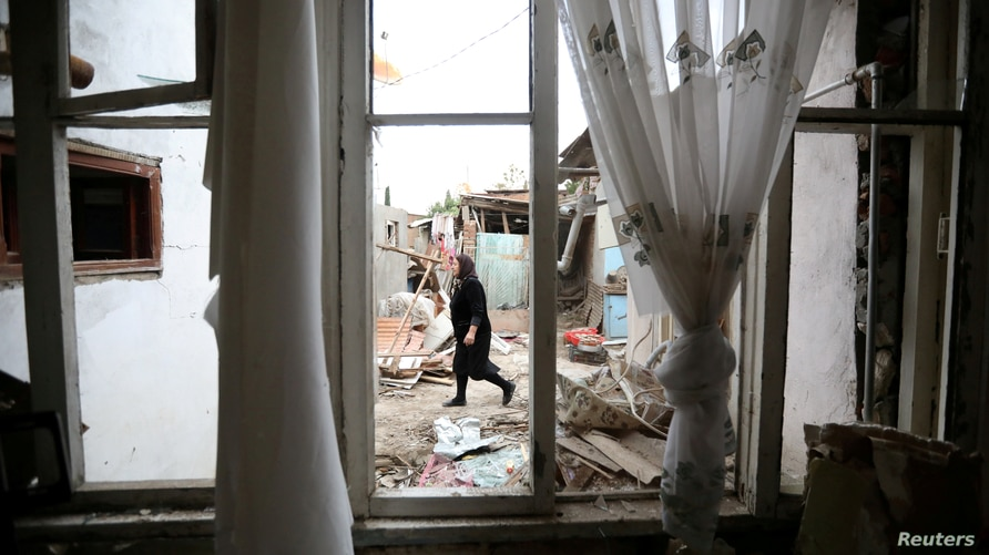 FILE PHOTO: A woman walks past a house damaged by recent shelling during a military conflict over the breakaway region of Nagorno-Karabakh, in Ganja