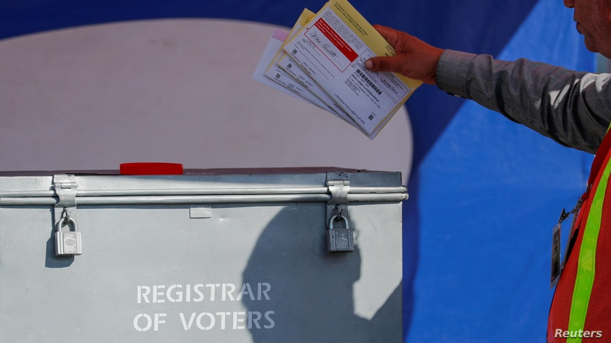 FILE PHOTO: An election worker places mail-in ballots into an election box at a drive-through drop off location at the Registrar of Voters in San Diego, California