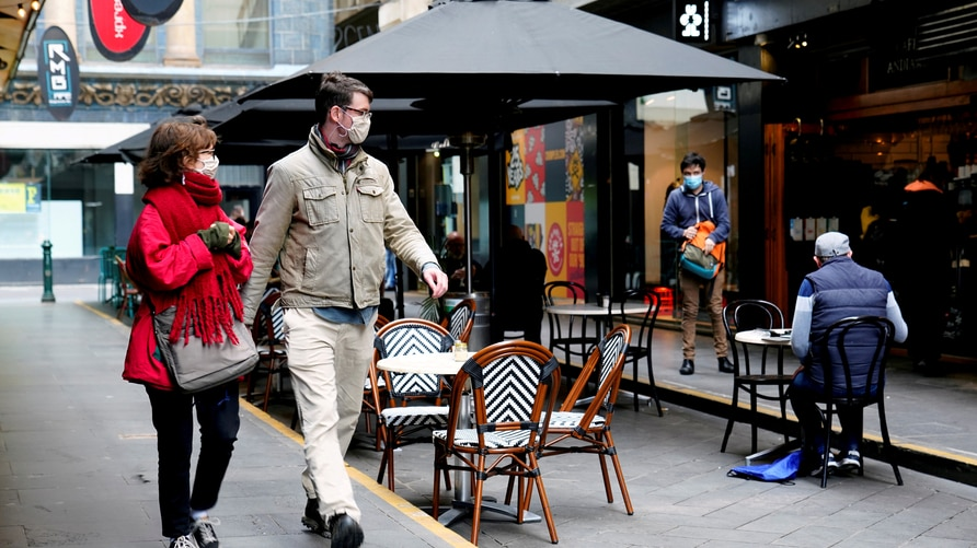 People walk past a cafe after the coronavirus disease (COVID-19) restrictions were eased for the state of Victoria, in Melbourne