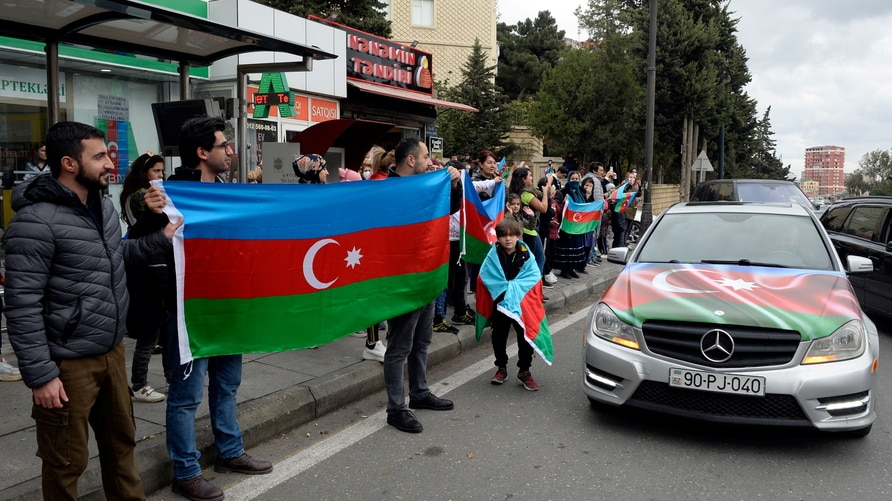 People celebrate on the streets after Azerbaijan's President Aliyev said the country's forces had taken Shusha (Shushi) during the fighting over the breakaway region of Nagorno-Karabakh, in Baku