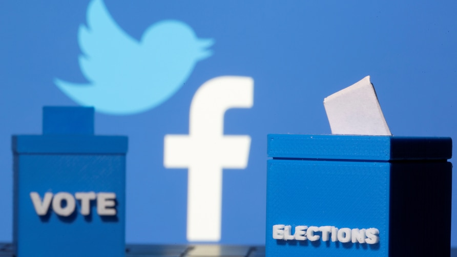 3D-printed ballot boxes are seen in front of Facebook and Twitter logos